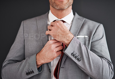 Buy stock photo Cropped shot of an unrecognizable middle aged bridegroom adjusting his necktie in preparation for his wedding