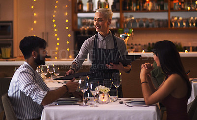 Buy stock photo Shot of a waitress serving a young couple in a restaurant