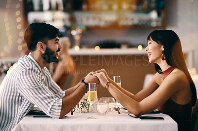 Buy stock photo Cropped shot of a young couple having wine while on a date