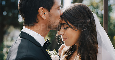 Buy stock photo Cropped shot of an affectionate young groom kissing his bride on her forehead on their wedding day