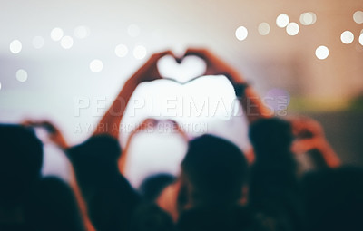 Buy stock photo Rearview shot of unrecognizable people making a heart shape while standing at a concert at night