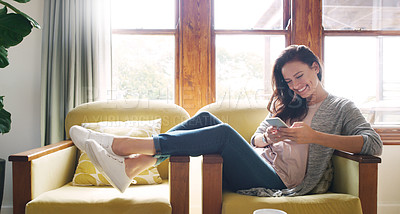 Buy stock photo Full length shot of an attractive young woman smiling while using a smartphone on her couch at home
