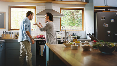 Buy stock photo Cropped shot of an affectionate young woman feeding her husband a spoonful of her food while cooking in their kitchen