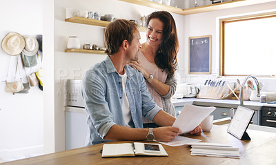 Buy stock photo Cropped shot of an affectionate young woman smiling at her husband while going through their budget at home