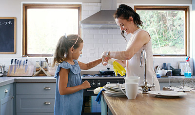 Buy stock photo Cropped shot of an affectionate young mother helping her daughter to put on rubber gloves while doing the dishes at home