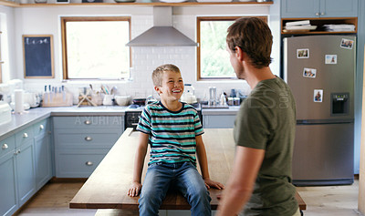 Buy stock photo Cropped shot of an affectionate young boy smiling at his father while sitting on the kitchen counter at home