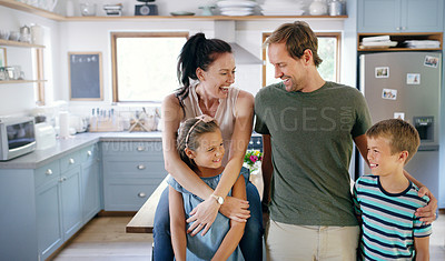 Buy stock photo Cropped shot of two affectionate young parents spending time with their kids in the kitchen at home