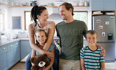 Buy stock photo Cropped shot of two affectionate young parents laughing together while spending time with their kids in the kitchen at home