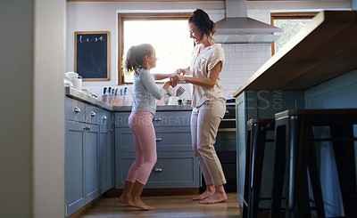 Buy stock photo Full length shot of an affectionate young mother dancing with her daughter in their kitchen at home