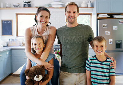 Buy stock photo Cropped portrait of two affectionate young parents looking cheerful while spending time with their two kids in their kitchen