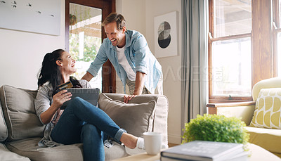 Buy stock photo Cropped shot of an affectionate young woman laughing with her husband while using a digital tablet to shop online at home