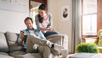 Buy stock photo Cropped shot of an affectionate young couple using a digital tablet and a credit card to shop online at home