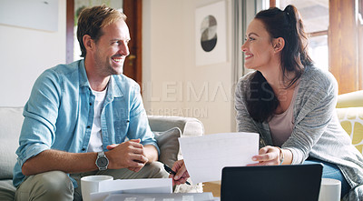 Buy stock photo Cropped shot of an affectionate young couple smiling at each other while going through their budget at home