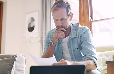 Buy stock photo Cropped shot of a handsome young man looking thoughtful while going through his budget at home