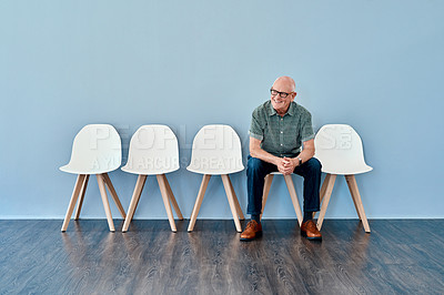 Buy stock photo Full length shot of a senior businessman sitting down and waiting in line against a blue background