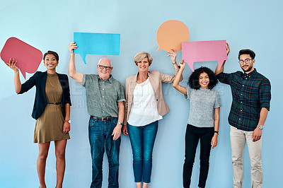 Buy stock photo Shot of a diverse group of businesspeople holding up speech bubbles against a blue background