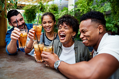 Buy stock photo Shot of a group of young friends sharing a toast and  enjoying themselves at an outdoor cafe