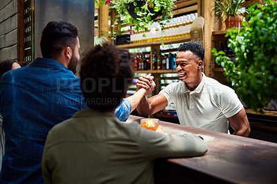 Buy stock photo Shot of a handsome young bartender shaking hands with a customer at his bar inside a modern cafe