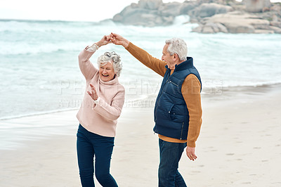 Buy stock photo Shot of a senior couple dancing together at the beach