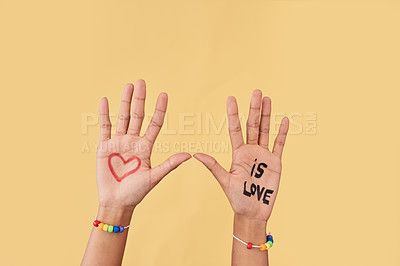 Buy stock photo Studio shot of an unrecognizable woman's palms raised up with love symbols and words painted on them
