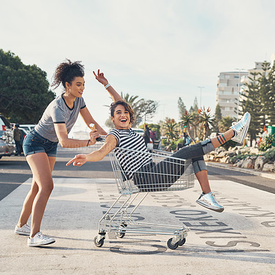Buy stock photo Shot of a young woman pushing her friend around on the promenade in a shopping chart