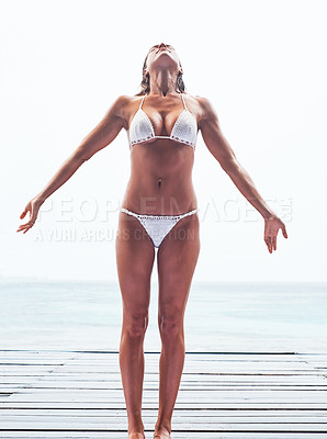 Buy stock photo Shot of a beautiful young woman posing in her bikini on the beach
