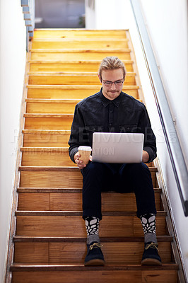 Buy stock photo Full length shot of a handsome young businessman sitting alone on the staircase alone and using his laptop