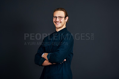 Buy stock photo Cropped portrait of a handsome young businessman standing alone with his arms folded against a black background in the studio