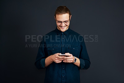 Buy stock photo Cropped shot of a handsome young businessman standing alone and texting on his cellphone against a black studio background