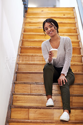 Buy stock photo Full length portrait of an attractive young businesswoman sitting on the office staircase and holding a cup of coffee