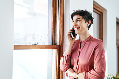 Buy stock photo Cropped shot of an attractive young businesswoman standing alone in the office and talking on her cellphone