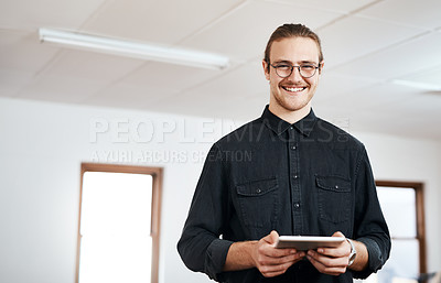 Buy stock photo Cropped portrait of a handsome young businessman standing and using a tablet in his office alone