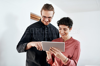 Buy stock photo Cropped shot of two young businesspeople standing together in the office and working on a tablet