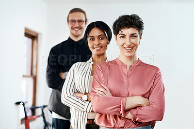 Buy stock photo Cropped portrait of a diverse group of businesspeople standing in a line with their arms folded in the office