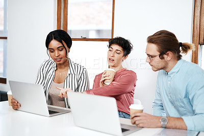 Buy stock photo Cropped shot of a diverse group of businesspeople sitting together and using their laptops during a meeting in the office