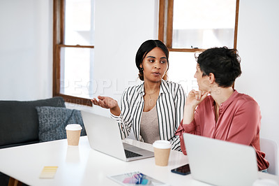 Buy stock photo Cropped shot of two young businesswomen sitting together in the office and using laptops during a meeting