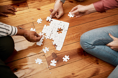 Buy stock photo High angle shot of an unrecognizable group of businesspeople sitting and doing a puzzle together in the office