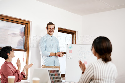 Buy stock photo Cropped shot of a handsome young businessman standing and writing on a white board while his colleagues clap for him
