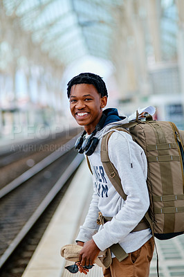 Buy stock photo Cropped portrait of a handsome young man standing alone and waiting for his train at the station