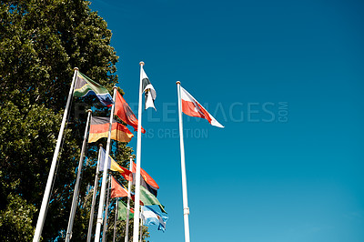 Buy stock photo Cropped shot of a group of national flags blowing in the wind during the day in Portugal