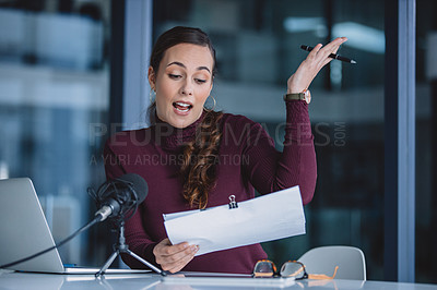 Buy stock photo Cropped shot of an attractive young businesswoman sitting alone and reading paperwork during a broadcasting in her office