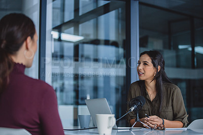 Buy stock photo Cropped shot of an attractive young businesswoman sitting in her office and being interviewed during a broadcasting