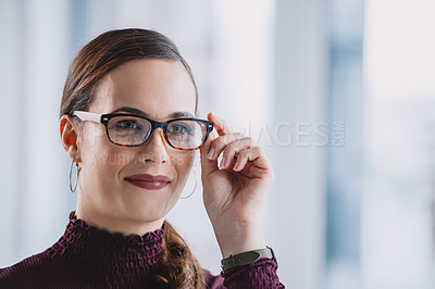 Buy stock photo Headshot of an attractive young businesswoman wearing spectacles and looking away while standing alone in her office