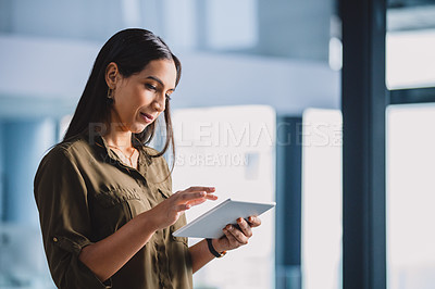 Buy stock photo Cropped shot of an attractive young businesswoman standing alone in her office and using a tablet