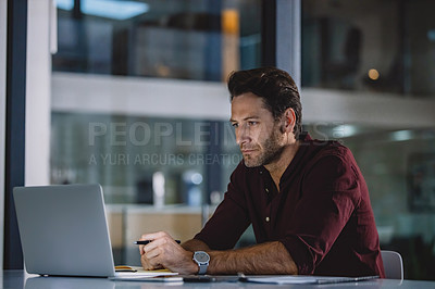Buy stock photo Cropped shot of a handsome mature businessman sitting alone in his office and using his laptop
