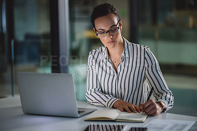 Buy stock photo Cropped shot of an attractive young businesswoman sitting alone in her office and writing out notes