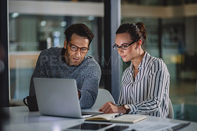 Buy stock photo Cropped shot of two business colleagues sitting together and using a laptop in the office late at night