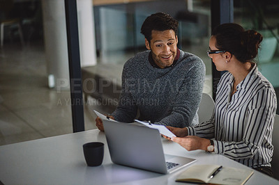 Buy stock photo Cropped shot of two business colleagues sitting together and using technology and paperwork during a meeting late at night