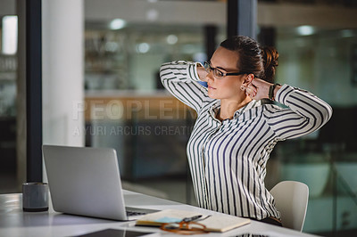Buy stock photo Cropped shot of an attractive young businesswoman feeling tired and stretching while sitting alone in her office late at night