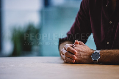 Buy stock photo Cropped shot of an unrecognizable businessman sitting alone in his office with his hands clasped together
